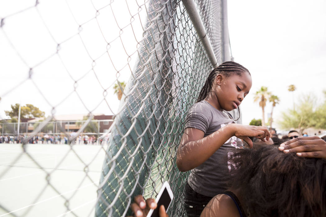 Jayana Powell, 7, braids her mom's hair while they wait in line over an hour to participate in the Back-to-School Fair hosted by Marianaճ Supermarkets at Clark High School in Las Vegas, Thur ...