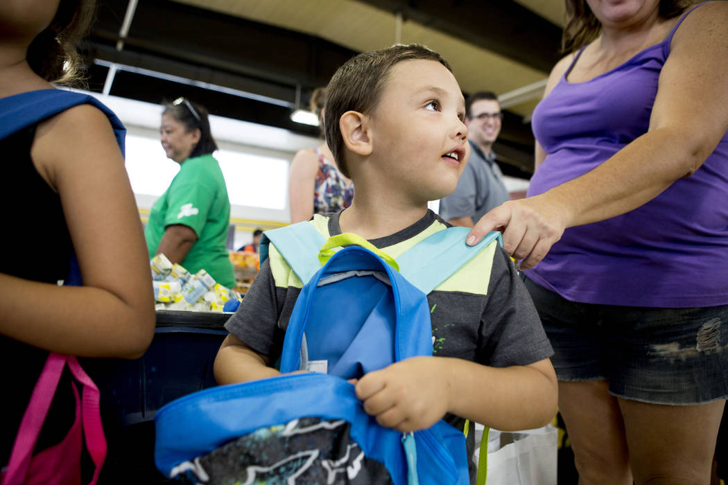 Victor Aguilar, 5, fills his new backpack with supplies during the Back-to-School Fair hosted by Marianaճ Supermarkets at Clark High School in Las Vegas, Thursday, Aug. 3, 2017.  People wait ...