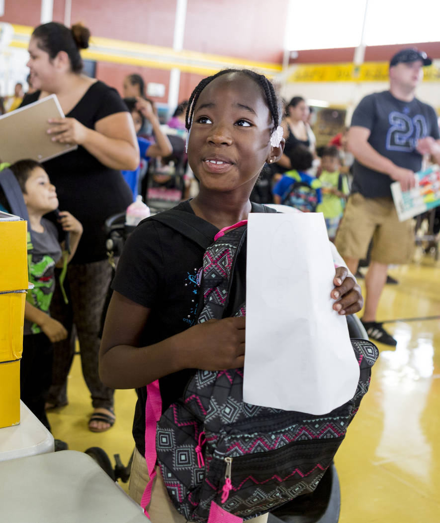 Kemonne Bradford, 8, fills her new backpack with supplies during the Back-to-School Fair hosted by Marianaճ Supermarkets at Clark High School in Las Vegas, Thursday, Aug. 3, 2017.  People wa ...