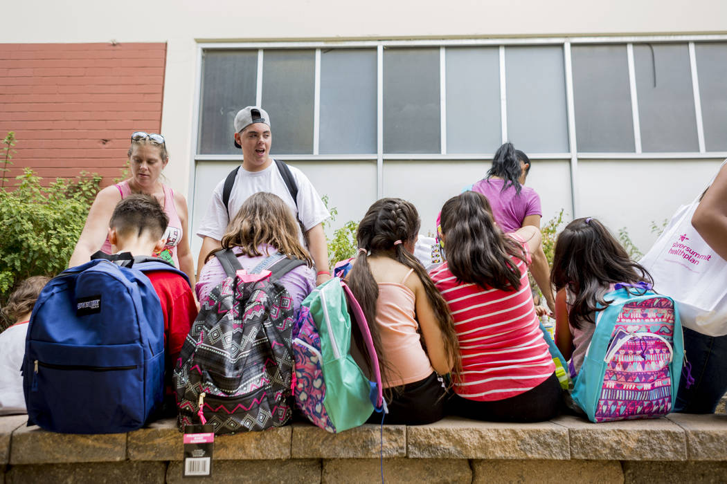 Students sit wearing their new backpacks received during the Back-to-School Fair hosted by Marianaճ Supermarkets at Clark High School in Las Vegas, Thursday, Aug. 3, 2017.  People waited out ...