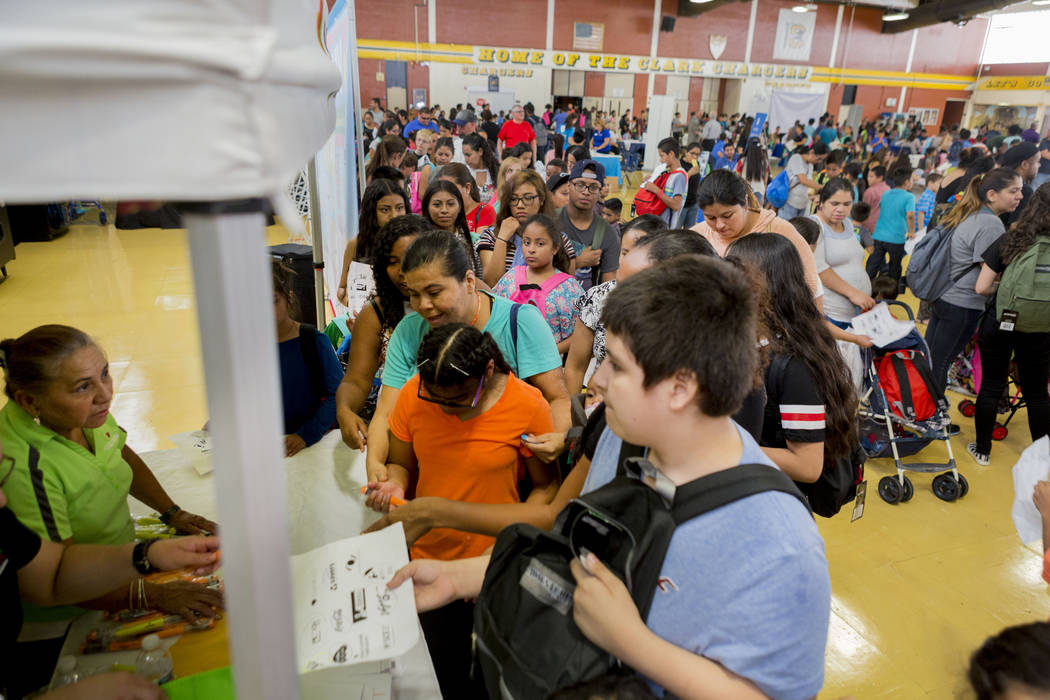 People wait inline to collect pens during the Back-to-School Fair hosted by Marianaճ Supermarkets at Clark High School in Las Vegas, Thursday, Aug. 3, 2017.  People waited outside for over a ...