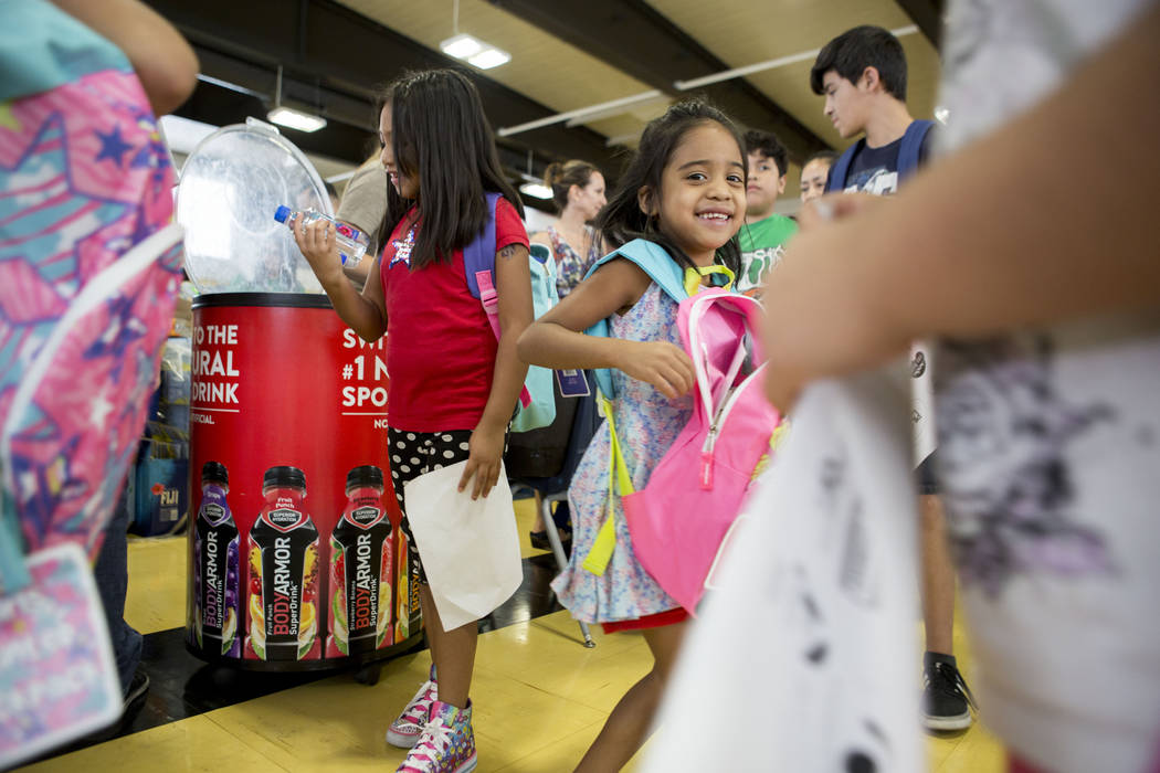 Snacks and school supplies are distributed during the Back-to-School Fair hosted by Marianaճ Supermarkets at Clark High School in Las Vegas, Thursday, Aug. 3, 2017.  People waited outside fo ...