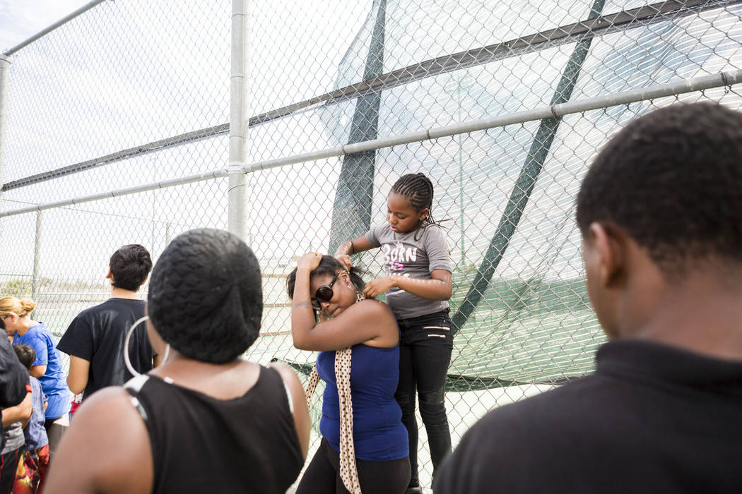Jayana Powell, 7,  braids Kiayana Powell's hair while they wait in line for over an hour to participate in the Back-to-School Fair hosted by Marianaճ Supermarkets at Clark High School in Las ...