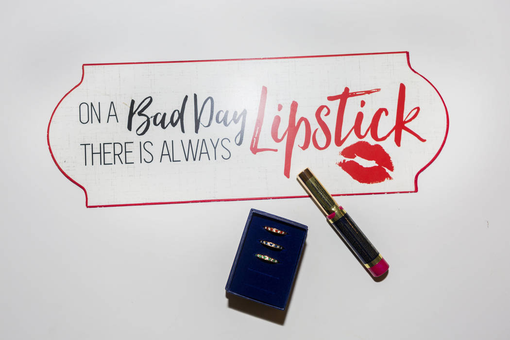 A sign on SeneGence distributor Teresa Isgriggs' desk along with rings that were gifts for reaching different ranks from SeneGence and tube of Lipsense in her home in Las Vegas, Wednesday, July 19 ...