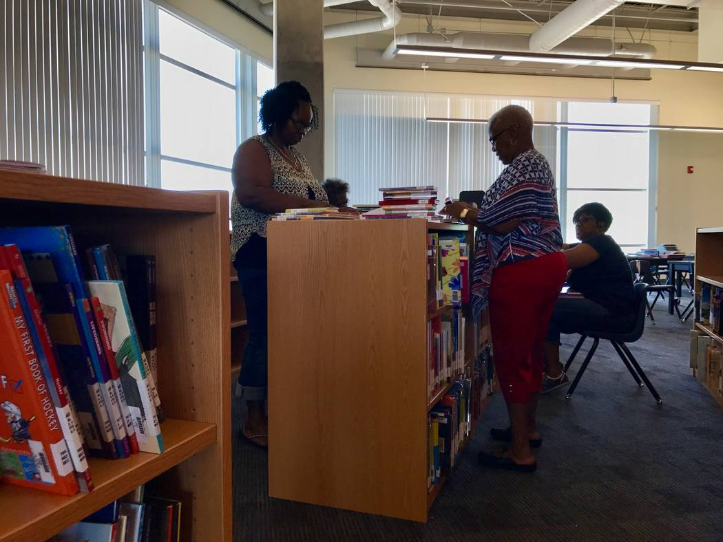 Volunteers help prepare and shelve books in the new library at Beverly S. Mathis Elementary School. (Madelyn Reese/View) @MadelynGReese