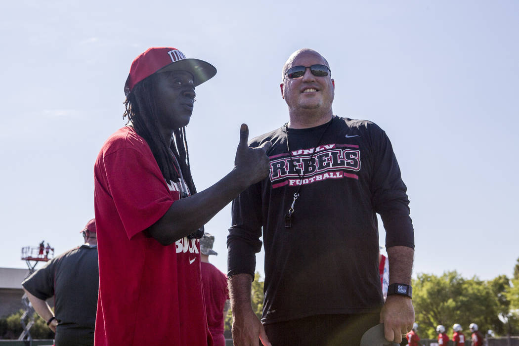 Rapper Flavor Flav talks to UNLV's head football coach, Tony Sanchez, during the first day of training camp at Rebel Park on Wednesday, August 2, 2017. Flavor Flav's godson Rashad Walker (#34), a  ...