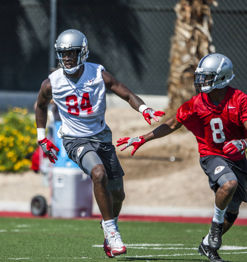 UNLV wide receiver Kendal Keys looks for a pass while running past defensive player Jocquez Kalili while scrimmaging during the first day of training camp at Rebel Park on Wednesday, August 2, 201 ...