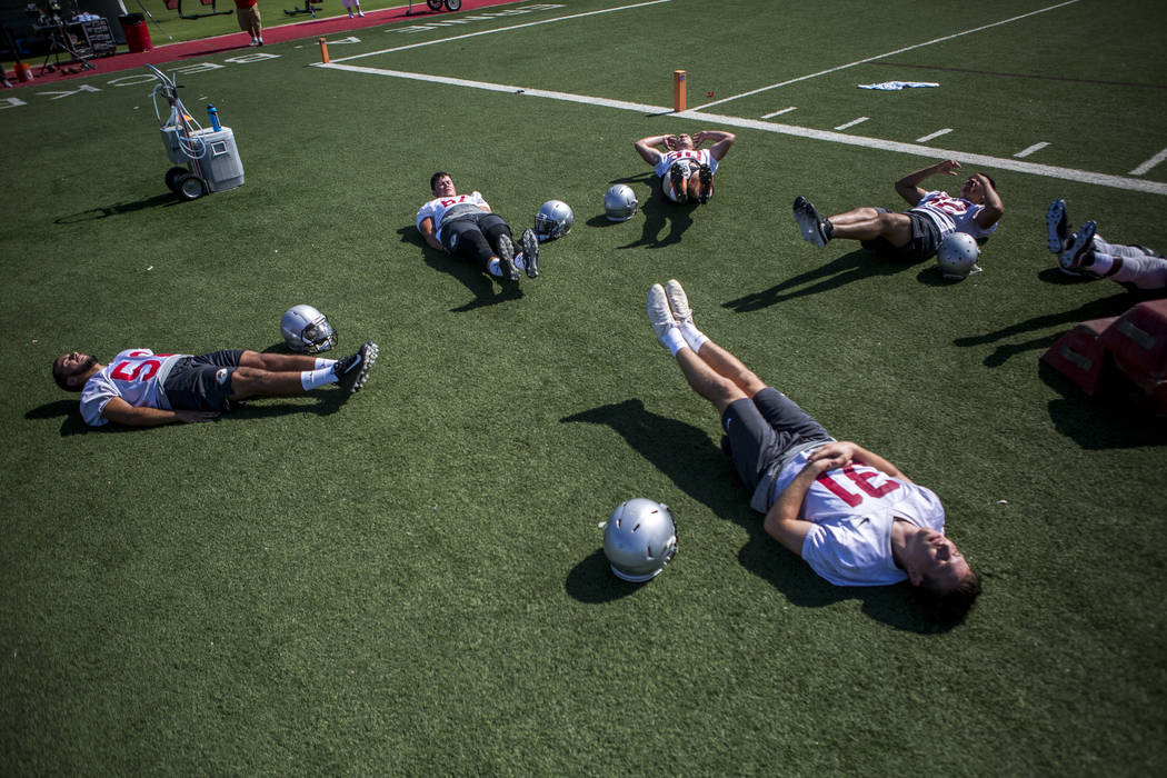 UNLV offensive players do leg lifts together during the first day of training camp at Rebel Park on Wednesday, August 2, 2017.  Patrick Connolly Las Vegas Review-Journal @PConnPie