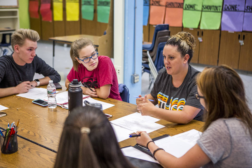 Student council members Chris Douglas, senior body president, left, Daniela Cassidy, first vice president, advisor Lindsay Powers, and Devon Neary, secretary, go through agenda items with the othe ...