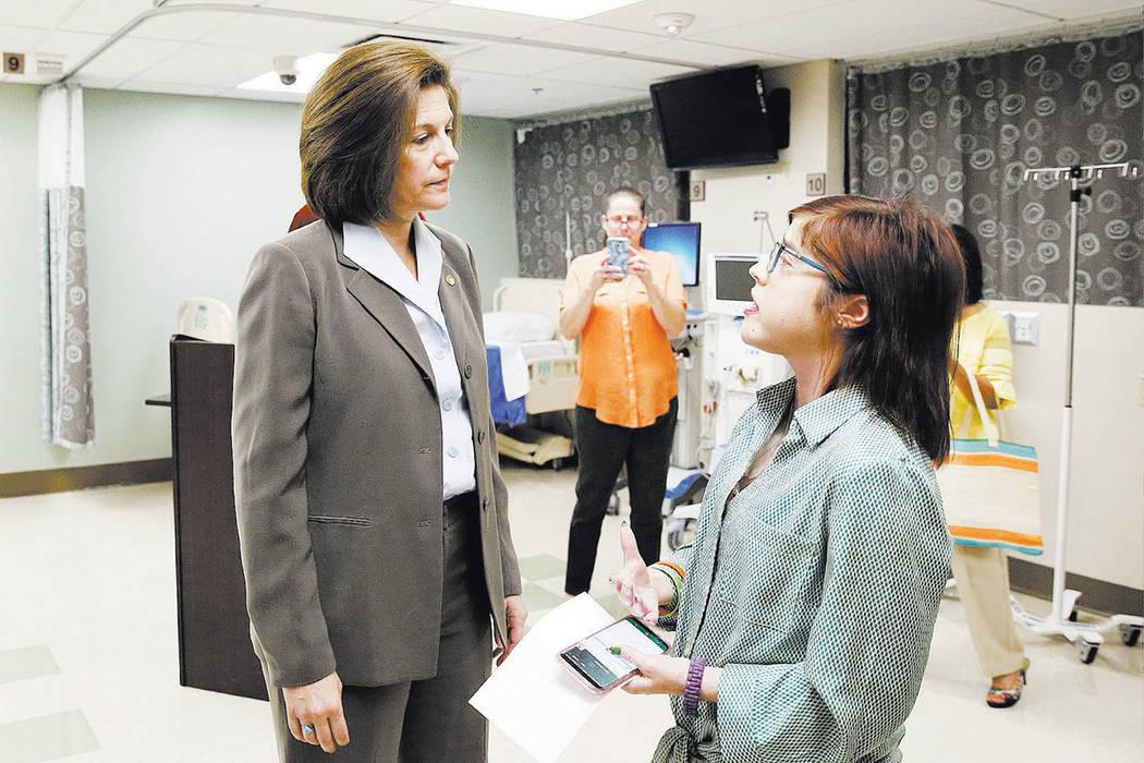 Karen Stiles, center, takes a photo as U.S. Sen. Catherine Cortez Masto, D-Nev., left, talks to her daughter Jenny after Masto held a press conference at University Medical Center on Friday, July  ...