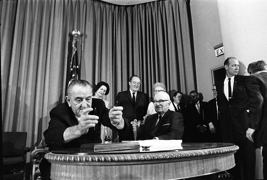 President Lyndon Johnson chooses between two pens to sign legislation that created the Medicare and Medicaid health care programs in this July 30, 1965 photo taken during a ceremony at the Harry S ...