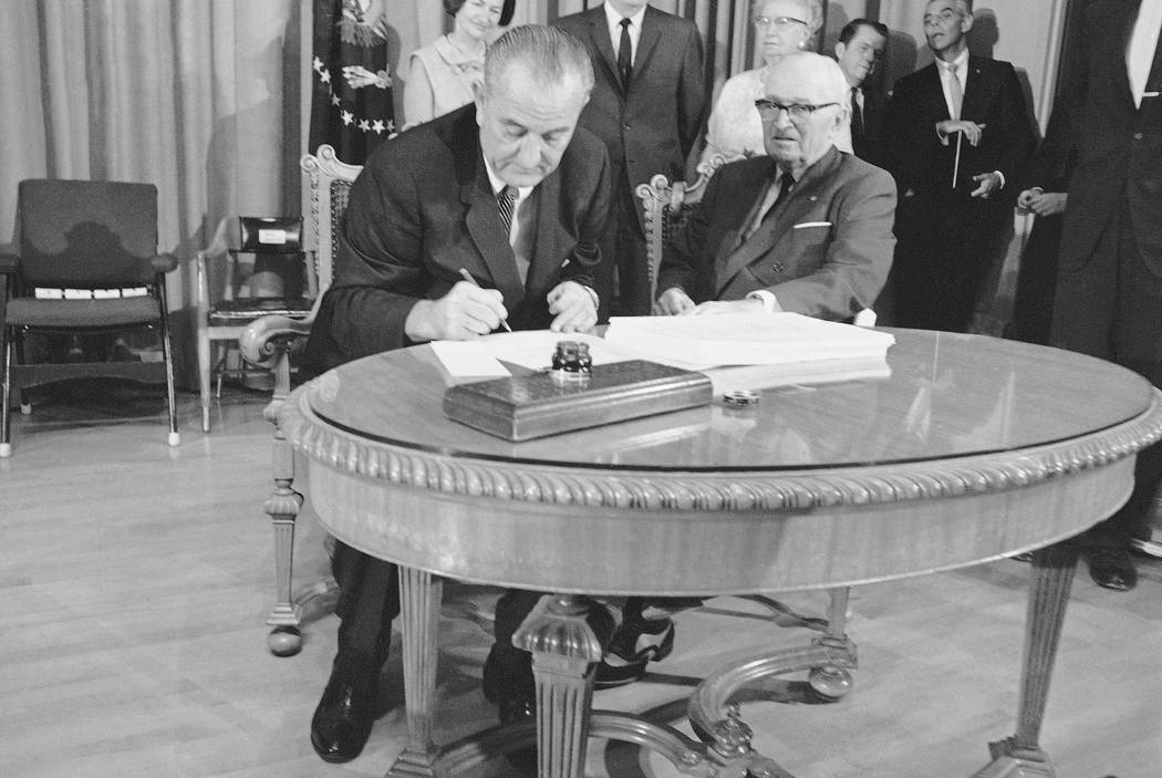 With former Pres. Harry S. Truman at his side, President Lyndon B. Johnson uses the last of many pens to complete the signing of the Medicare Bill into law at ceremonies at the Truman Library in I ...