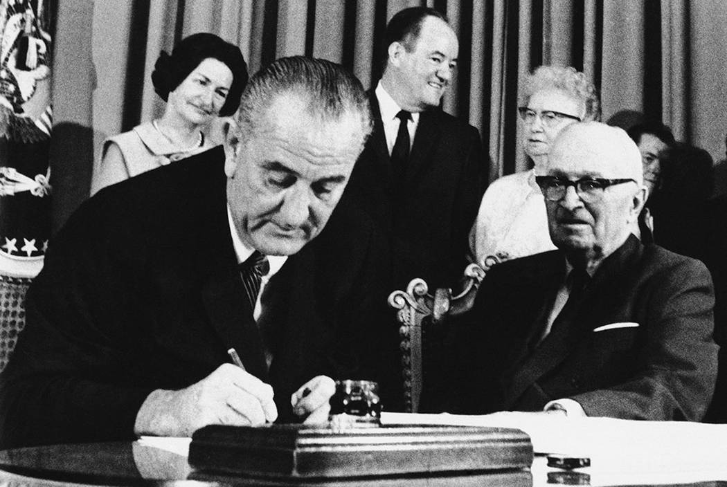 President Lyndon Johnson signs the Medicare Bill into law while former President Harry S. Truman, right, observes during a ceremony at the Truman Library in Independence, Mo., on July 30, 1965. At ...
