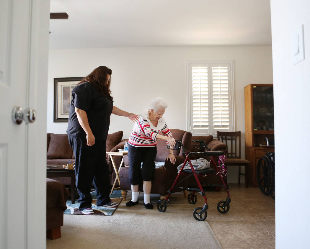 Physical care attendant Renee Nadeau assists Mary Jones, 88, in Jones' home in Las Vegas, Tuesday, Aug. 1, 2017. Jones is a client of a non-medicinal care, Golden Heart Senior Care, where she has  ...