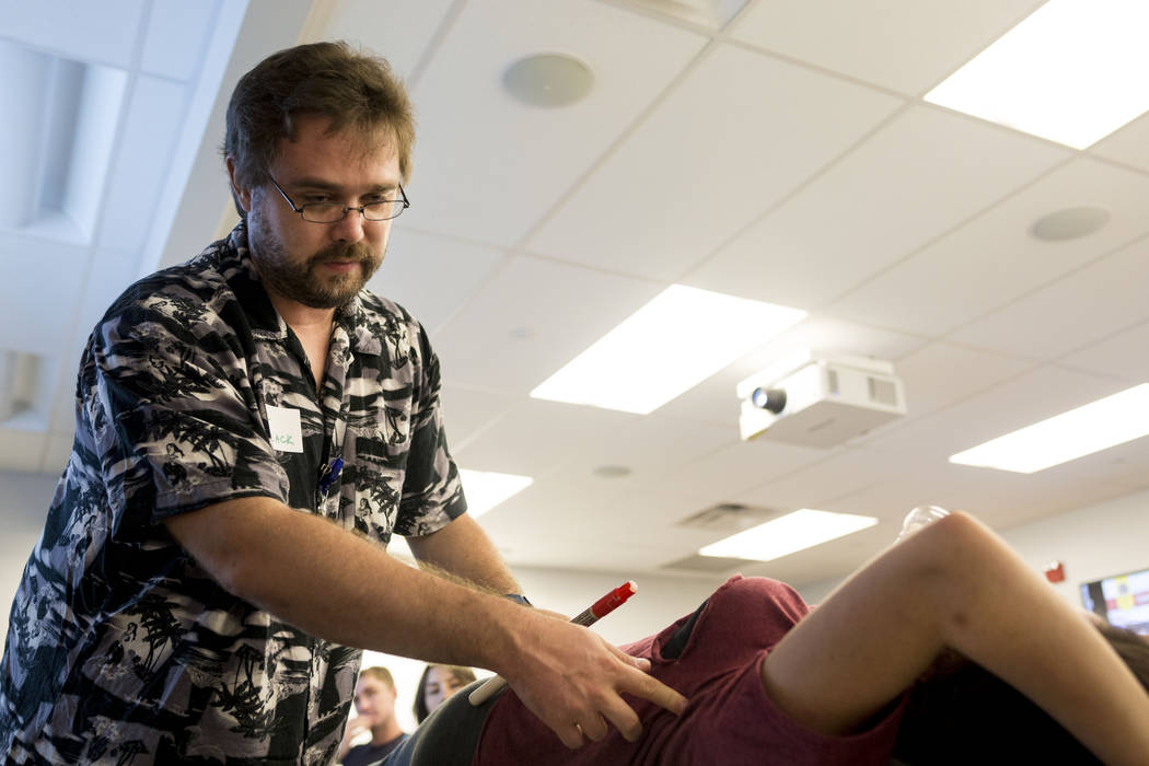 Resident Nick Schulack assesses Gigi Perez, a young actress wearing makeup to look like she's been the victim of a stabbing during a UNLV graduate medical education class for resident physicians a ...