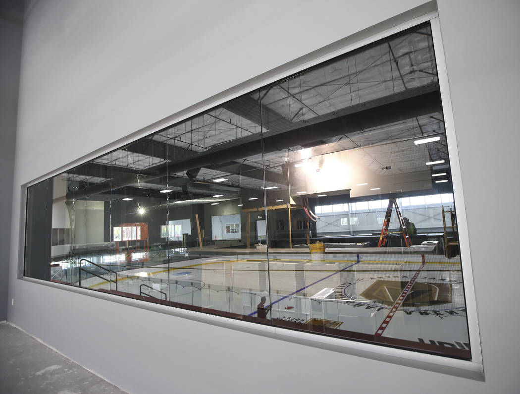 Finishing touches are applied to the ice surface of one of two ice rinks, seen reflected in the window, at City National Arena, the Vegas Golden Knights' headquarters and training facility, in Las ...