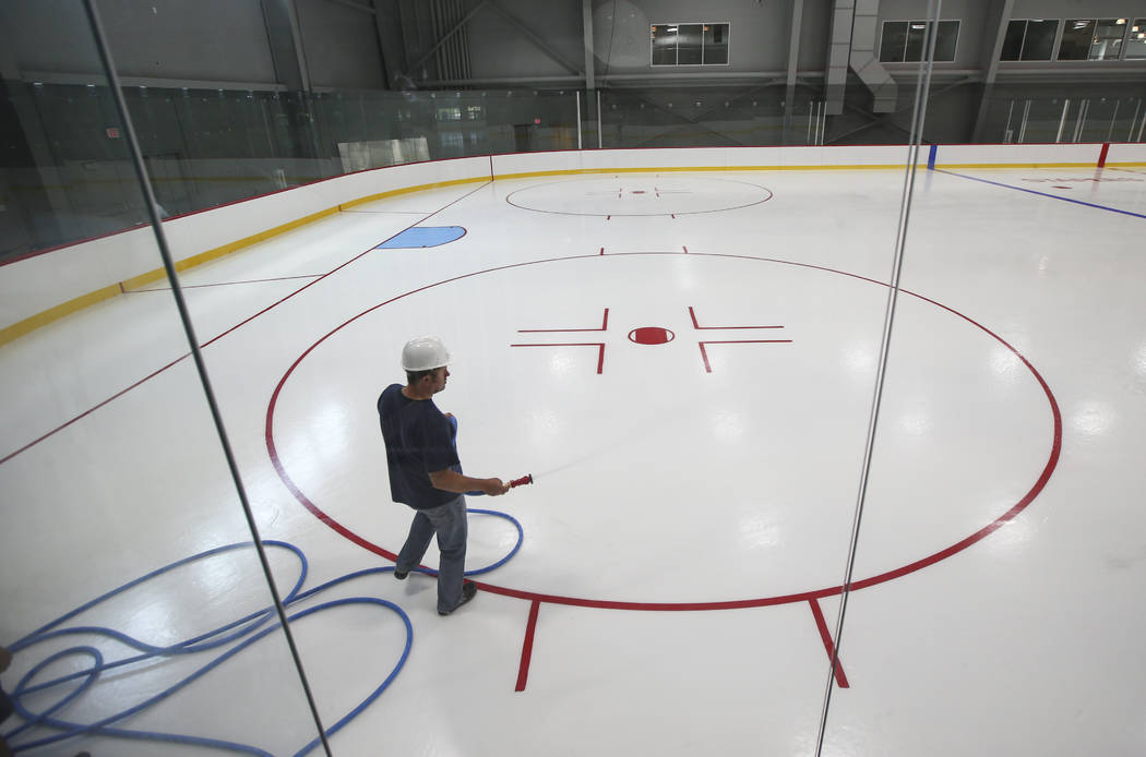 A member of the ice crew puts on the finishing touches on the ice surface of one of two ice rinks at City National Arena, the Vegas Golden Knights' headquarters and training facility, in Las Vegas ...