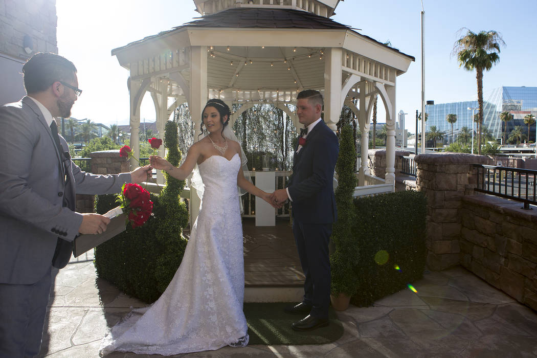 Rev. Tony Velasquez, left, hands roses to Rebecca Poncsak, center, and Scott Deutscher, right, during their wedding ceremony at Vegas Weddings in Las Vegas on Saturday, Aug. 12, 2017. Bridget Benn ...