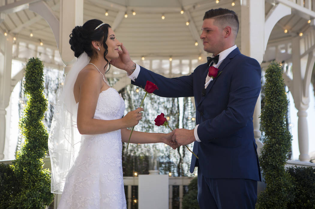 Rebecca Poncsak, left, and Scott Deutscher hold roses after exchanging rings during their wedding ceremony at Vegas Weddings in Las Vegas on Saturday, Aug. 12, 2017. Bridget Bennett Las Vegas Revi ...