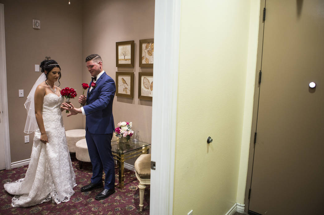 Newlyweds Rebecca Poncsak, left, and Scott Deutscher take a look at his ring after their ceremony at Vegas Weddings in Las Vegas on Saturday, Aug. 12, 2017. Bridget Bennett Las Vegas Review-Journa ...