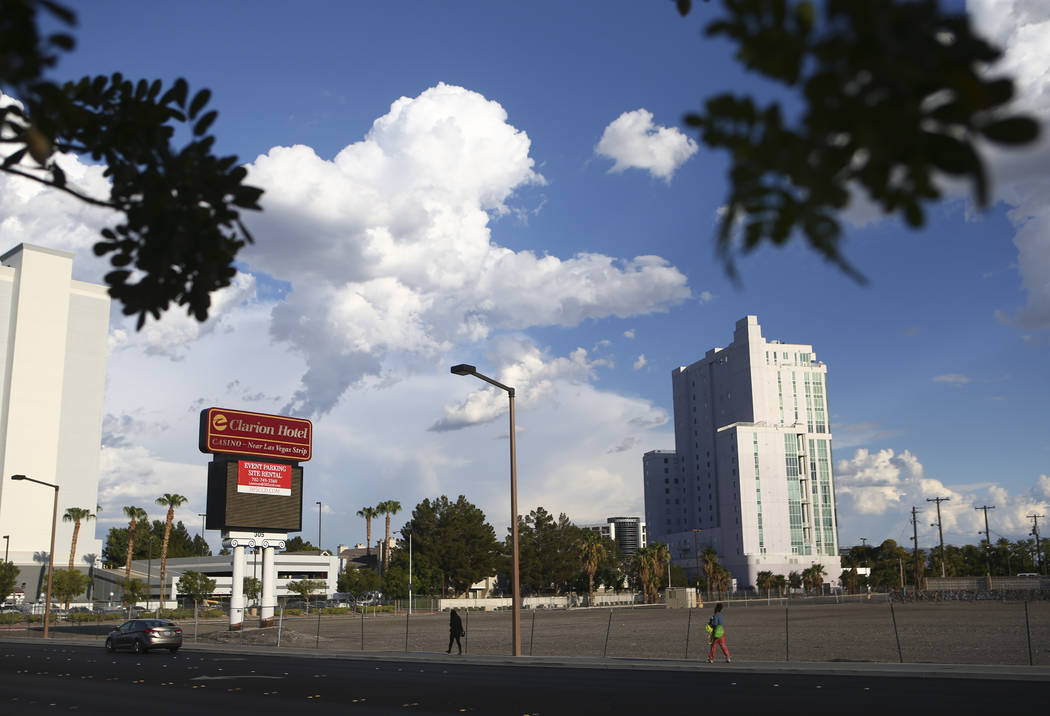 People walk by the lot where The Clarion Hotel and Casino once stood on Convention Center Drive in Las Vegas on Wednesday, Aug. 2, 2017. Chase Stevens Las Vegas Review-Journal @csstevensphoto