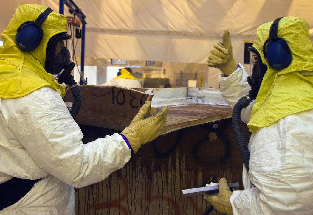 Crews repackage waste from a fiberglass reinforced plywood box into a container that can be shipped to the Waste Isolation Pilot Plant. U.S. Department of Energy