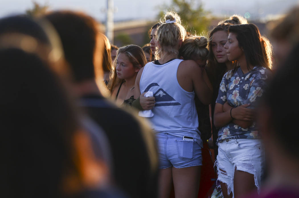 People embrace during a vigil for Haylei Hughes, a former Cimarron-Memorial student-athlete, who died in a hiking accident in Wash., at Kellogg Zaher Sports Complex in Las Vegas on Thursday, July  ...