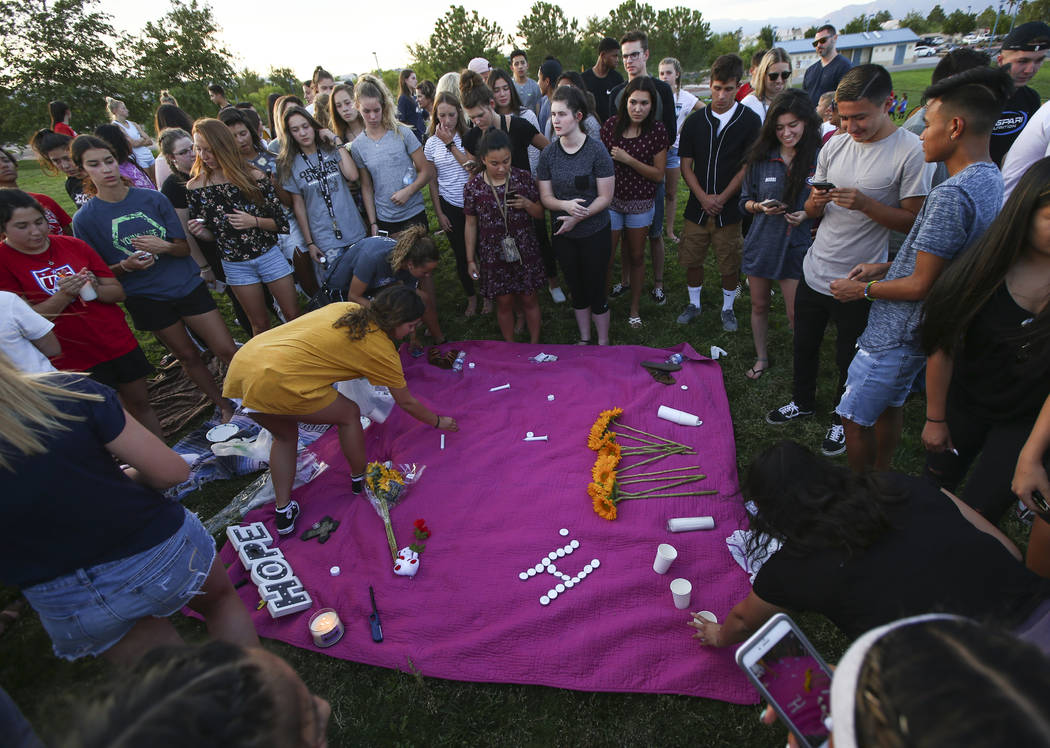 Savannah Day, left, in yellow, assists as people leave items behind during a vigil for Haylei Hughes, a former Cimarron-Memorial student-athlete, who died in a hiking accident in Wash., at Kellogg ...