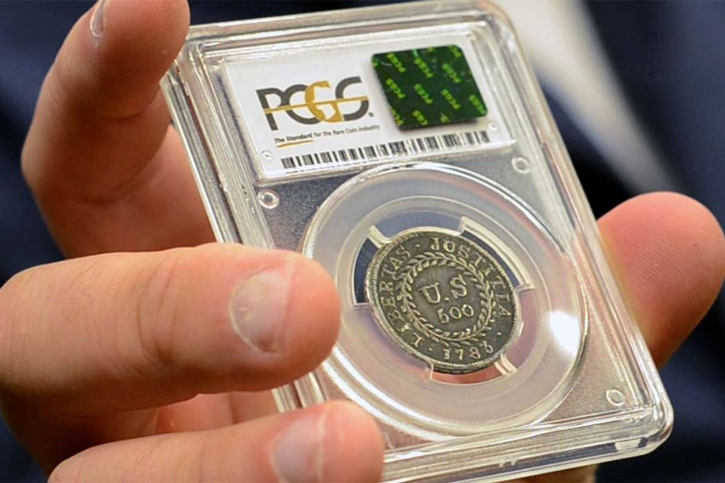 In this Monday, July 31, 2017, image made from a video, David McCarthy, a senior numismatist at Kagin's, holds what is believed to be the first coin ever struck by the U.S. government at the World ...