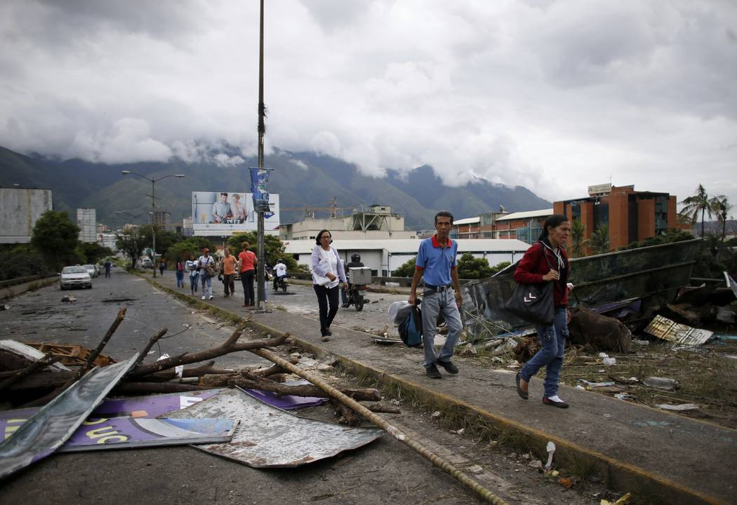 Pedestrians walk past a barricade made by anti-government demonstrators, in Caracas, Venezuela, Monday, July 31, 2017. Electoral authorities said more than 8 million people voted Sunday to create  ...