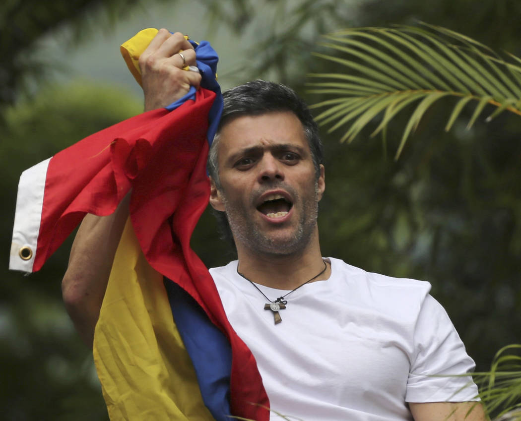 FILE - In this Saturday, July 8, 2017, file photo, Venezuela's opposition leader Leopoldo Lopez holds a national flag as he greets supporters outside his home in Caracas, Venezuela, following his  ...