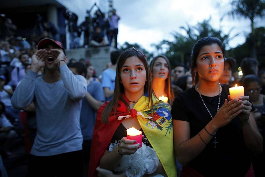 Anti-government demonstrators hold candles during a vigil in honor of those who have been killed during clashes between security forces and demonstrators in Caracas, Venezuela, Monday, July 31, 20 ...