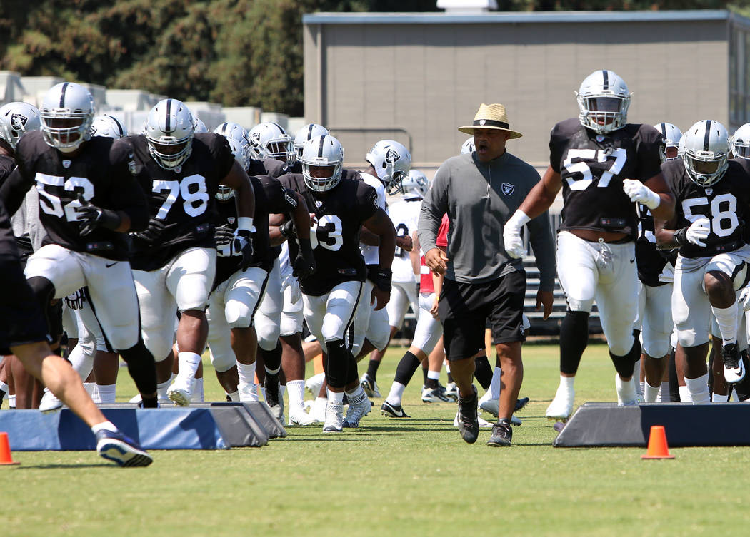 The Oakland Raiders defensive end Khali Mack (52) followed by defensive tackle Justin Ellis (78) and linebacker Cory James (57) run through obstacles during teams practice at Raiders Napa Valley t ...