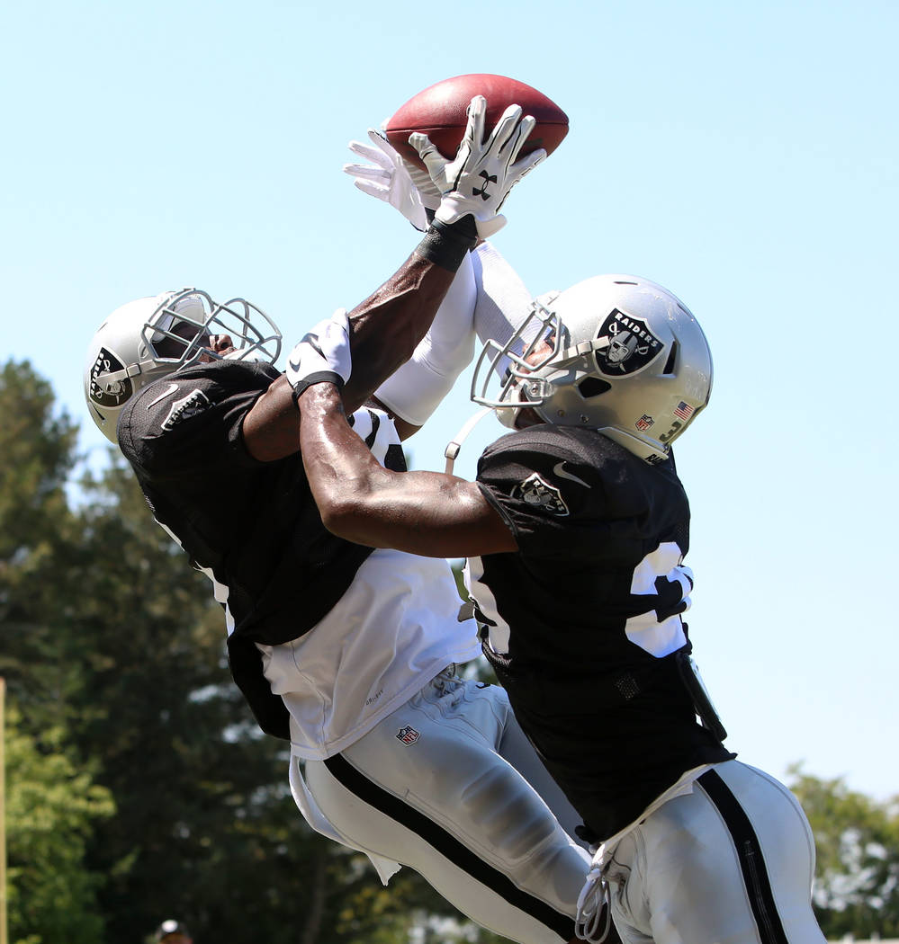 The Oakland Raiders cornerback Chris Humes, left, tries to catch a pass over cornerback TJ Carrie during teams practice at Raiders Napa Valley training complex in Napa, Calif., on Tuesday, Aug. 1, ...