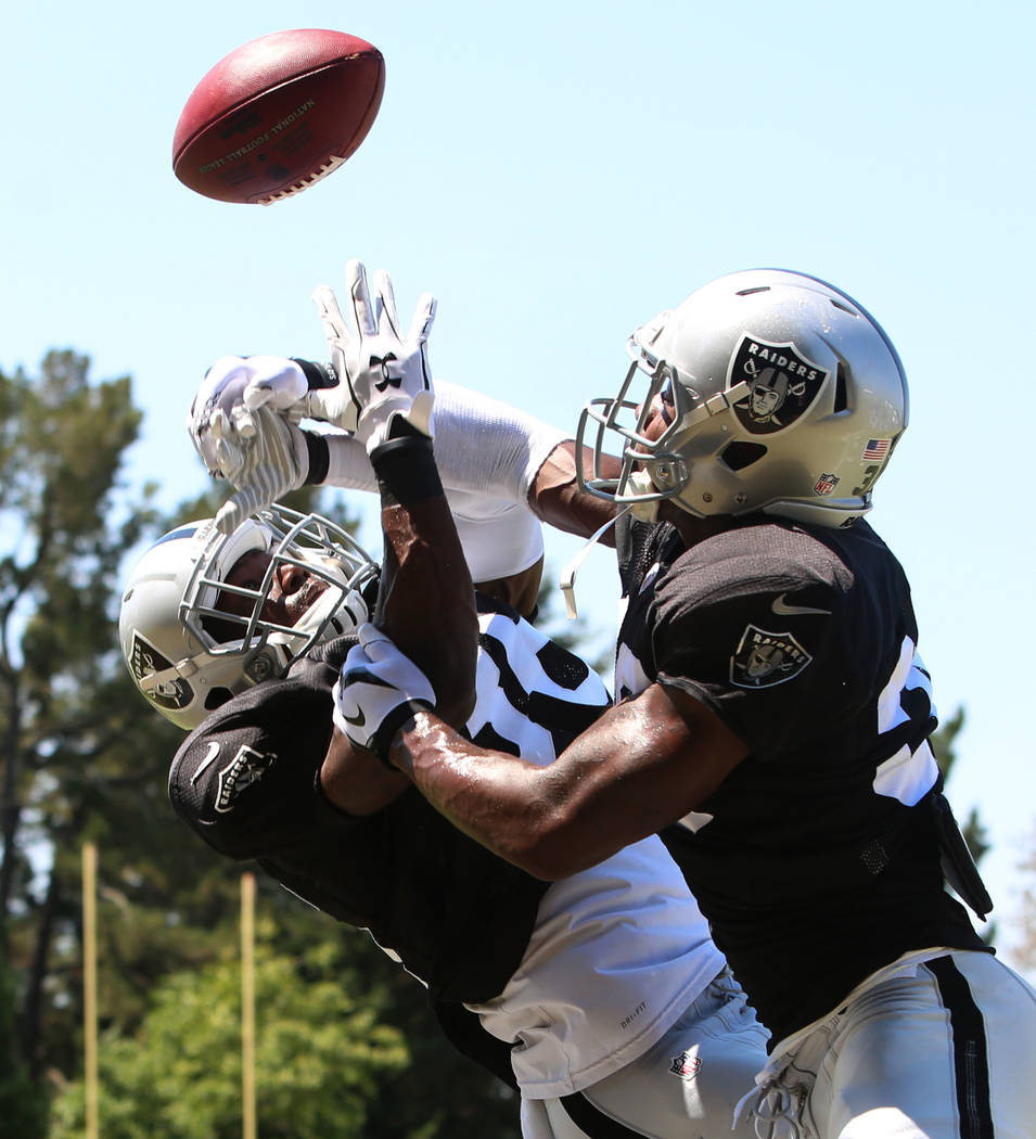 The Oakland Raiders cornerback TJ Carrie, right, knocks the ball away from cornerback Chris Humes during teams practice at Raiders Napa Valley training complex in Napa, Calif., on Tuesday, Aug. 1, ...