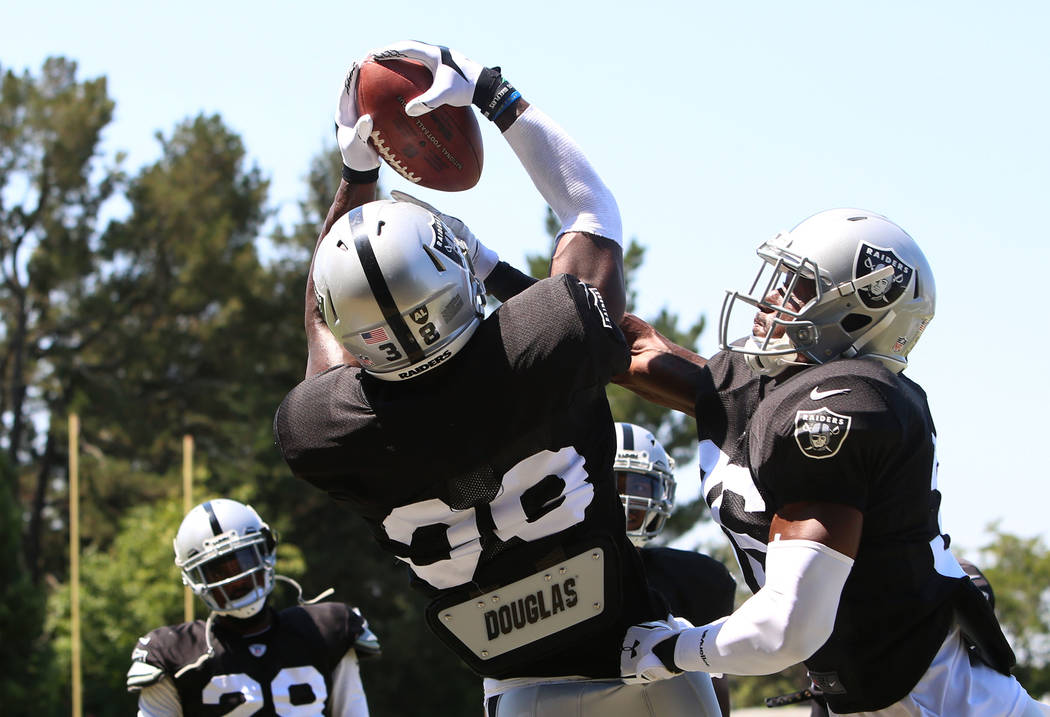 The Oakland Raiders cornerback TJ Carrie (38) catches a pass over cornerback Chris Humes, right, during teams practice at Raiders Napa Valley training complex in Napa, Calif., on Tuesday, Aug. 1,  ...
