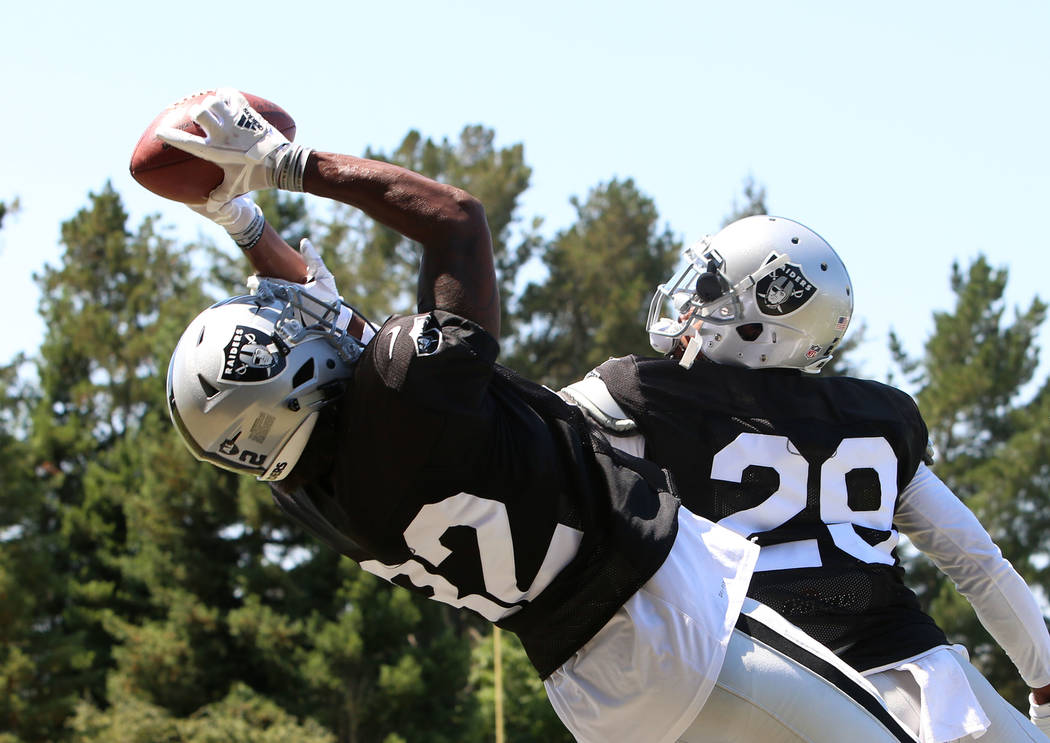 The Oakland Raiders cornerback David Amerson (29) tries to defend as cornerback Antonio Hamilton (32) catches a pass during teams practice at Raiders Napa Valley training complex in Napa, Calif.,  ...