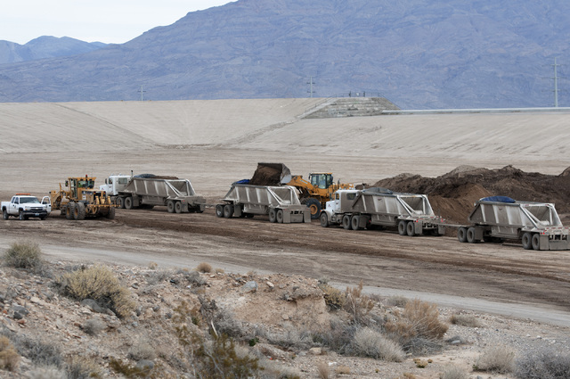 Trucks line up to transport debris accumulated in Kyle Canyon Detention Basin near Grand Teton Drive and Shaumber Road in Las Vegas to Apex landfill Tuesday, Jan. 21, 2014. The debris came from fl ...