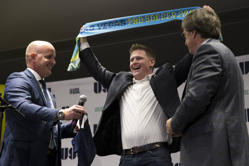 United Soccer League president Jake Edwards, left, and CEO Alec Papadakis, right, look on as Brett Lashbrook, founder of Las Vegas Soccer LLC, celebrates his new Las Vegas soccer team to play in t ...