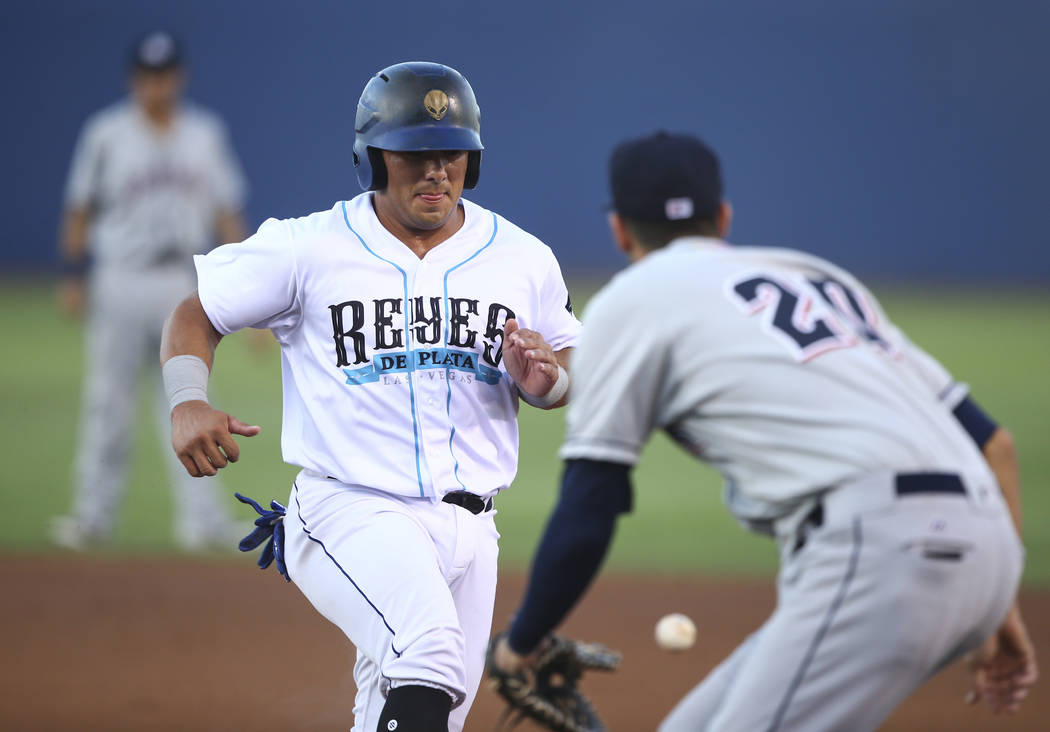 "Las Vegas 51s' Phillip Evans returns to first base to avoid being tagged out by the Colorado Springs Sky Sox during the debut of the ""Reyes de Plata"" (Silver Kings), part of a ne ..."