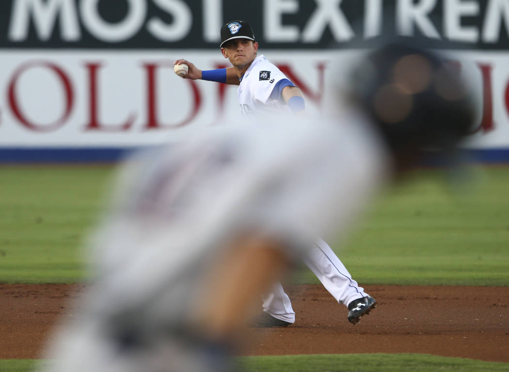 "Las Vegas 51s' Gavin Cecchini throws to first base to tag out Colorado Springs Sky Sox' Mauricio Dubon (13) during the debut of the ""Reyes de Plata"" (Silver Kings), part of a new ..."