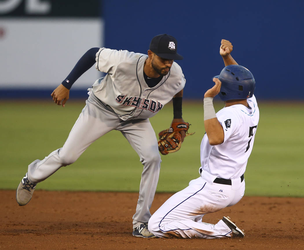 "Colorado Springs Sky Sox' Yadiel Rivera tags out Las Vegas 51s' Josh Rodriguez (7) during the debut of the ""Reyes de Plata"" (Silver Kings), part of a new Minor League Baseball in ..."