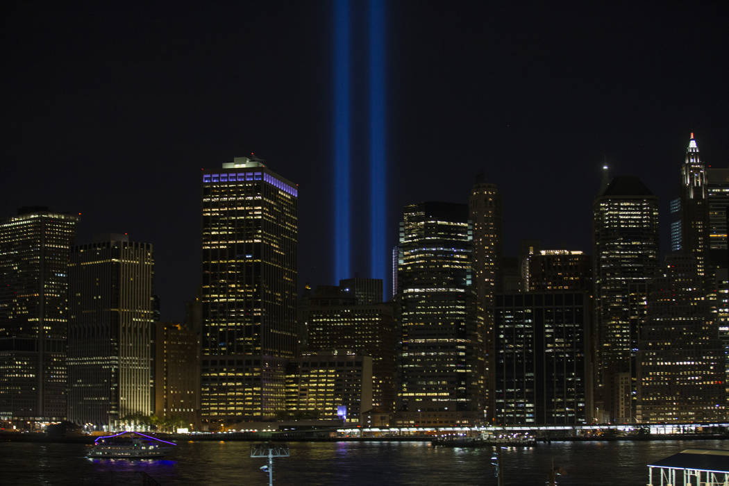 Blue beams of the Tribute of Light pierce the air over near the National September 11 Memorial and Museum in the Manhattan borough, seen from the Brooklyn borough in New York on Sunday, Sept. 11,  ...
