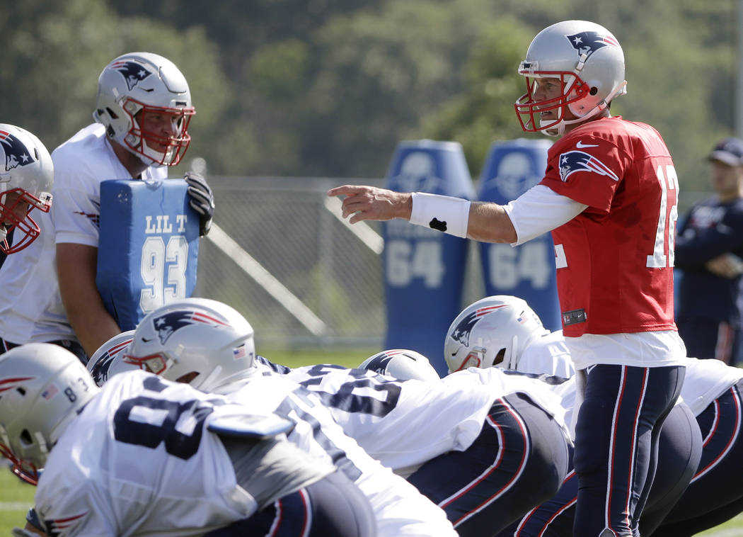 New England Patriots quarterback Tom Brady (12), right, on the line at NFL football training camp, Tuesday, Aug. 1, 2017, in Foxborough, Mass. (AP Photo/Steven Senne)