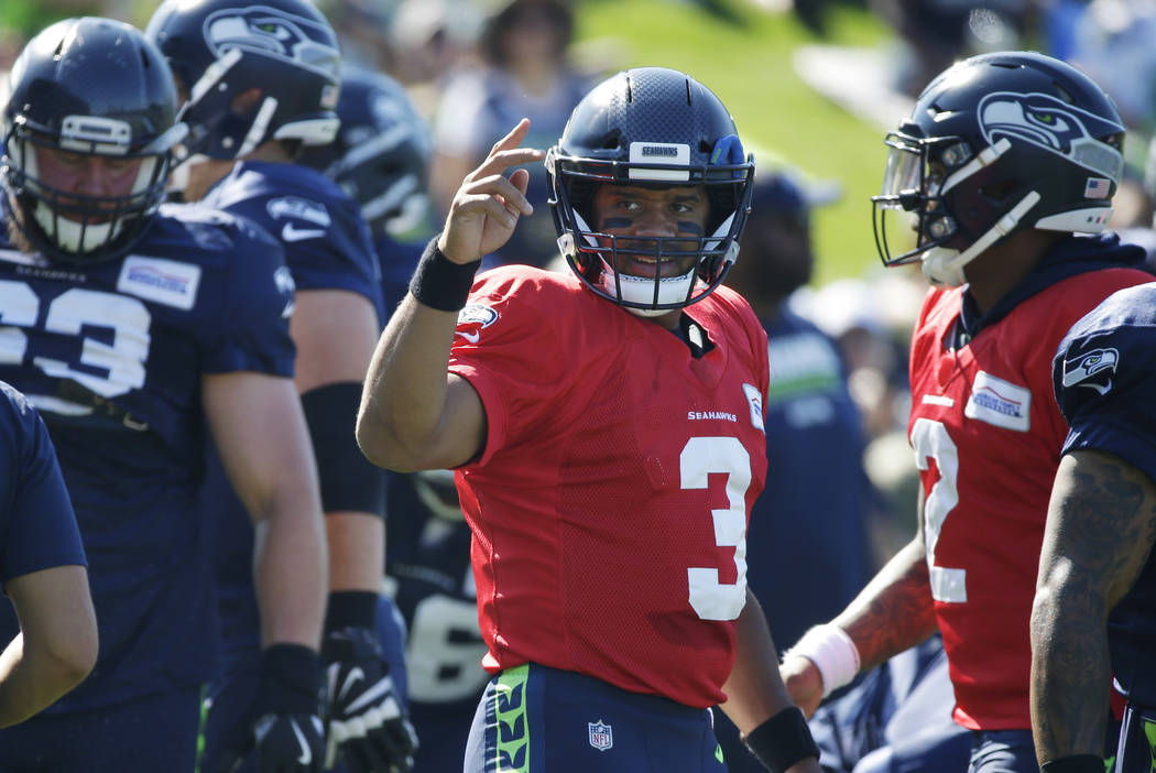 Seattle Seahawks quarterback Russell Wilson (3) makes a salute gesture to a fan during NFL football training camp, Tuesday, Aug. 1, 2017, in Renton, Wash. (AP Photo/Ted S. Warren)