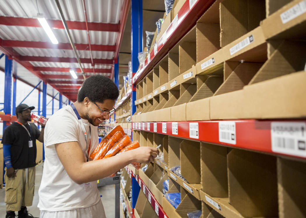 Warehouse employee Deonte Woods organizes athletic team logo knit hats at the Fanatics distribution center in North Las Vegas, Wednesday, Aug. 16, 2017. (Elizabeth Brumley/Las Vegas Review-Journal)