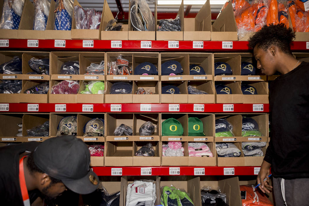 Warehouse athletes Marcus Davis, left, and Anthony Davis organize athletic team logo hats at the Fanatics distribution center in North Las Vegas, Wednesday, Aug. 16, 2017. (Elizabeth Brumley/Las V ...