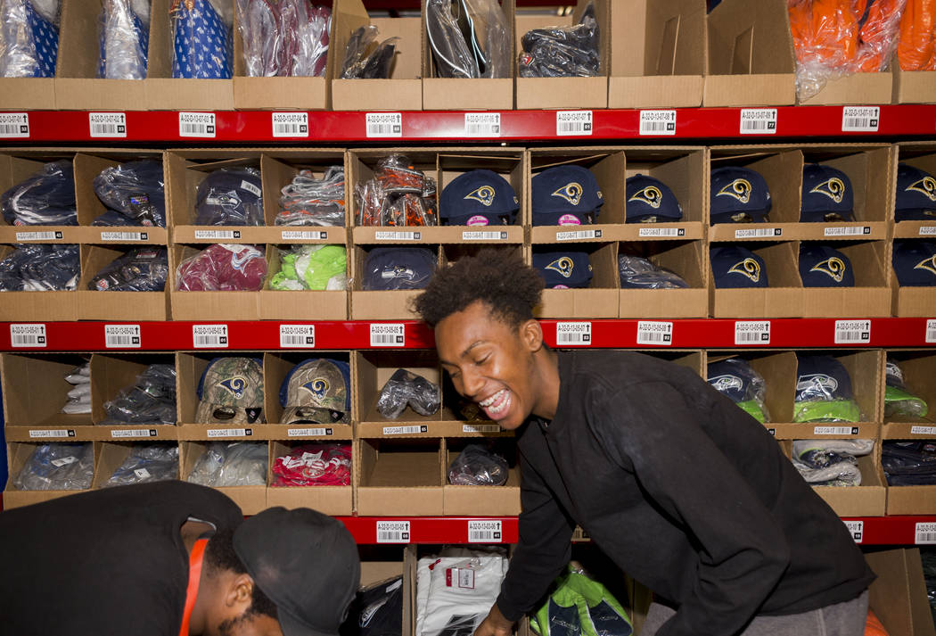 Warehouse athletes Marcus Davis, left, and Anthony Davis organize athletic team logo hats at the Fanatics distribution center in North Las Vegas, Wednesday, Aug. 16, 2017. (Elizabeth Brumley/Las V ...