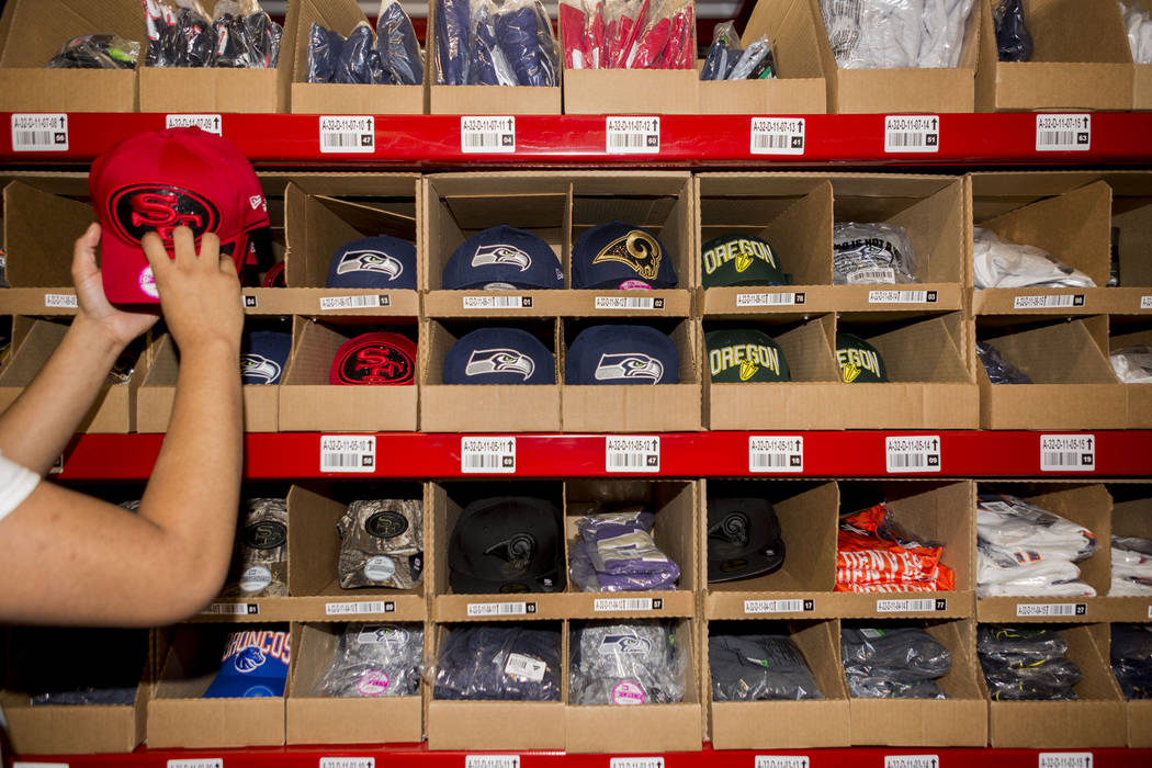 Warehouse employee Deonte Woods organizes athletic team logo hats at the Fanatics distribution center in North Las Vegas, Wednesday, Aug. 16, 2017. (Elizabeth Brumley/Las Vegas Review-Journal)
