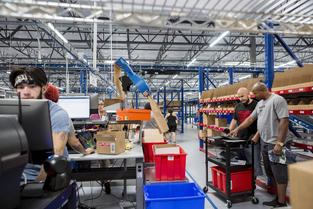 Warehouse employees work on packing athletic logo inventory at the Fanatics distribution center in North Las Vegas, Wednesday, Aug. 16, 2017. (Elizabeth Brumley/Las Vegas Review-Journal)